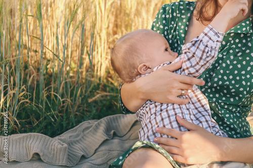 Fotografía  Woman breastfeeding her little son outdoors