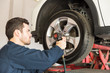 Worker Using Impact Wrench On Change Tire