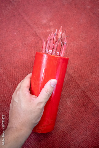 Photo  Hand holding a Chi-Chi Stick, Fortune stick or Seam Si at Chinese shrine in Thailand