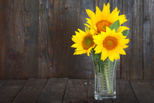 Bouquet Of Sunflowers In Glass Vase On Dark Wooden Background. Still Life Image With Copy Space.