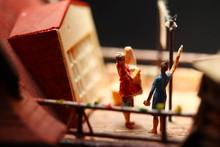 Miniature Figure Model Scene Of Housekeeper Do Laundry Work On Rooftop House Model.