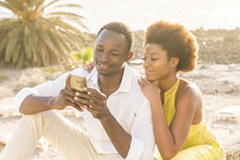 Happy Black Young Couple At The Beach With Sunset Backlight On The Background, Smile And Laugh Using A Smartphone To Chat With Friends Or To See Pictures Of The Vacation