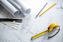 Yellow Tape Measure (measuring Tape), Scale And Pencils On Architectural Drawing Plan Of House Project, Blueprint Rolls On Working Table, Architecture Drawing Tools And Building Construction Concepts