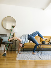 Woman Bending Over Backwards Sweeping And Dusting