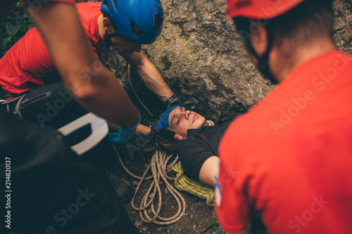 Photo Search and rescue team helping injured alpinist