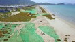 People picking seaweed and drying on sea shore drone view. Aerial landscape blue sea and seaweed drying on coast.