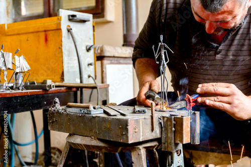 Artist is making figure by welding few metal wires in his workshop, barehanded