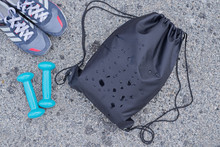 Black Drawstring Backpack, Bag For Sport And Fitness, Sneakers And Dumbbells On The Ground