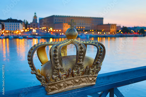 Staande foto Stockholm Golden crown on Skeppsholm bridge with illuminated Stockholm old city center Gamla Stan in the background during twilight sunset.