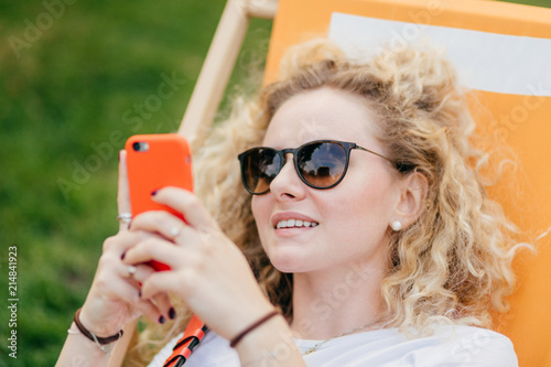 Fotografie, Obraz  Outdoor shot of pleasant looking curly young female in sunglasses, holds modern