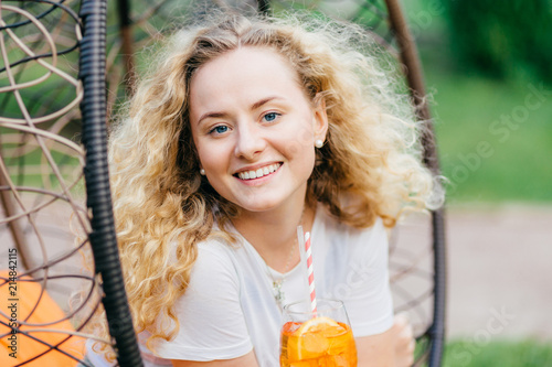 Horizontal shot of pretty smiling European female has wavy bushy light hair, holds fresh cocktail, sits on hanging chair, breathes fresh air. Positive emotions, recreation and people concept