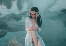 A Lonely Mermaid, Sitting On A Rock In The Middle Of The River, Which Was Tightened By A Thick, Impenetrable Fog. On The Sea Nymph A White Vintage Dress With Bare Legs And A Wreath Of Shells
