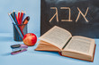 ABC letters written in Hebrew. Concept of education or back to school. An open book, apple and set of colored pencils.