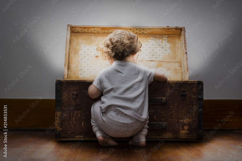 Fototapety, obrazy: An adorable little child dressed in pajamas with diaper sticking out looks into a mysterious bright treasure chest.