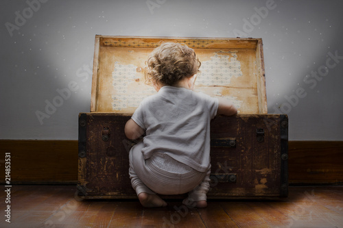 Leinwand Poster An adorable little child dressed in pajamas with diaper sticking out looks into a mysterious bright treasure chest