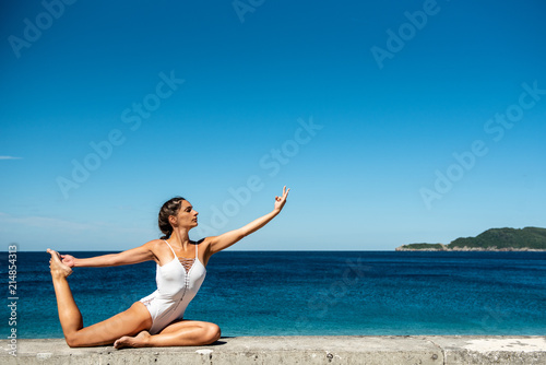 Fotografia  Attractive woman in her 40s, practicing yoga on sea side, doing One Legged King Pigeon Pose - Eka Pada Rajakapotasana,  in white swimsuit, with sea in the background