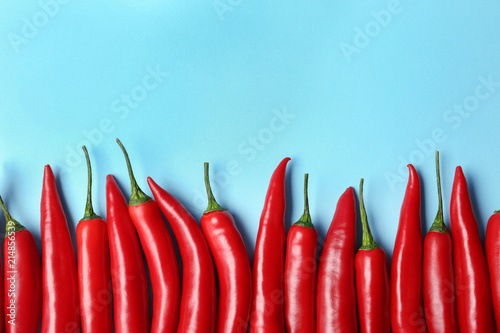 Flat lay composition with chili peppers on color background