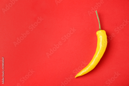 Ripe hot chili pepper on color background, top view