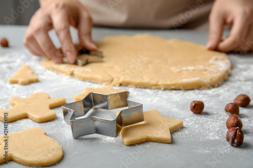 Young woman preparing Christmas cookies on table