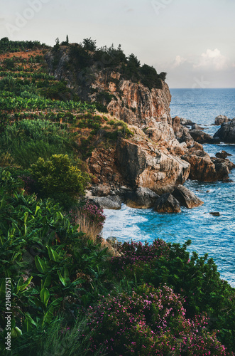 Keuken foto achterwand Kust Beautiful natural landscape with blue sea, sky, green hills with blooming trees and rocks. Hidden turquoise bay in Mediterranean coast of Turkey