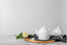 Tray With Teapot And Rose On Table Against Light Background