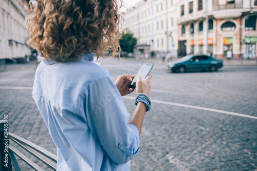 Fotografía  Rear view unrecognizable curly young woman using smart phone