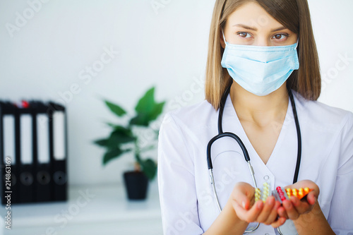 Clinic. Portrait of young doctor standing in medical office Poster