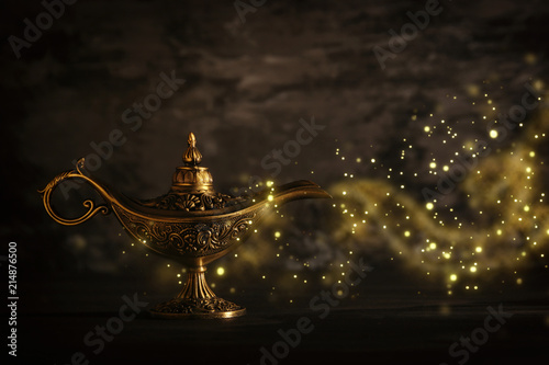 Fotografia  Image of magical mysterious aladdin lamp with glitter sparkle smoke over black background