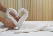 Close-up Of Hands Putting Folded Swans Bird Of Fresh White Bath Towels On The Bed Sheet In The Hotel