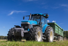Modern Blue Tractor In The Field