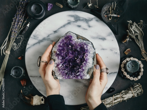 Photo The witch is holding amethyst stone surrounded magic things