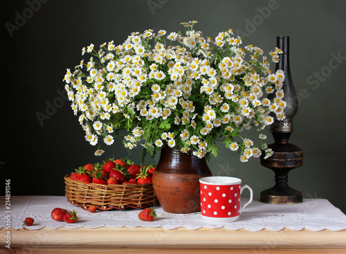 Fototapeta Strawberries and daisies. Still life with a bouquet of flowers and berries. obraz