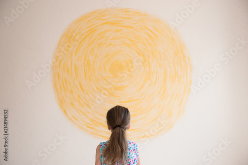 Foto  little caucasian girl looking at yellow sun painted on wall indoors