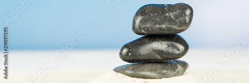 Foto op Plexiglas Stenen in het Zand Three black stones in the sand, blue sky background, square