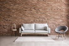 Modern Interior Of Living Room With Comfortable Sofa And Armchair Near Brick Wall