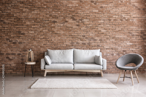 Modern interior of living room with comfortable sofa and armchair near brick wal Wallpaper Mural