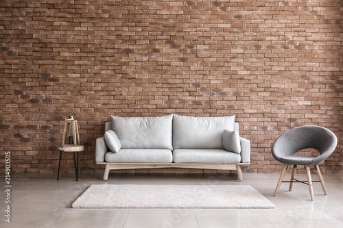 Fotografija Modern interior of living room with comfortable sofa and armchair near brick wal