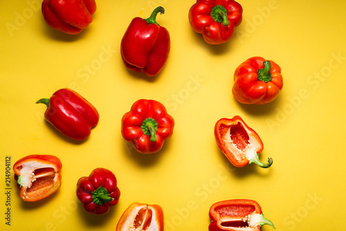 Carta da parati Fresh red bell peppers on bright yellow background, top view