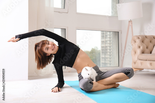 Foto op Aluminium Ontspanning Sporty woman with bunny practicing yoga at home