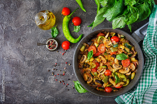 Hot spicy stew eggplant, sweet pepper, tomato, zucchini and mushrooms. Flat lay. Top view