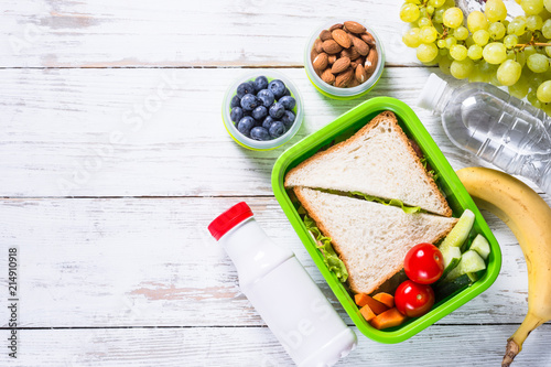 Assortiment Lunch box with sandwich, vegetables, yogurt, nuts and berries.