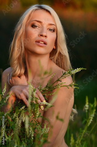 Poster Akt Blonde girl walking outdoor on the river bank at sunset