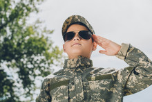 Portrait Of Little Boy In Camouflage Clothing And Sunglasses Saluting With Cloudy Sky On Backdrop