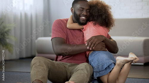 Foto  Little daughter tightly hugging beloved daddy, excellent relationship in family