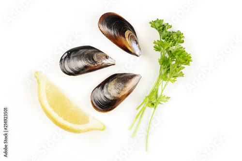 Foto op Plexiglas Schaaldieren Overhead photo of three raw mussels on white with lemon, parsley, and copy space