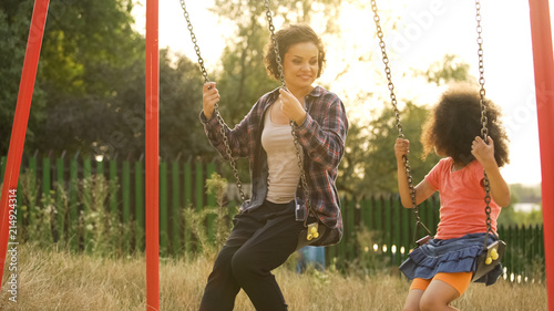 Two cheerful sisters swinging together at outdoor child playground, happiness