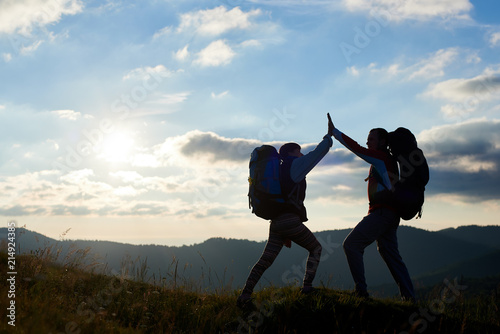 Photo  Silhouette of happy couple with backpacks on top of the mountain give each other a high five against the background of the mountains and the cloudy sky with a bright sun at sunset