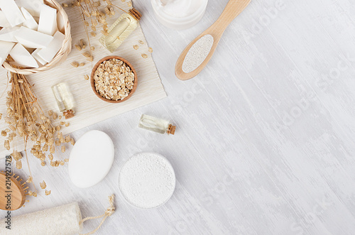 Fototapeta Organic homemade white cosmetics and raw oatmeal flakes, massage oil, bath accessories on light beige wooden background, flat lay