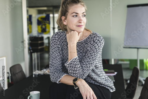 Young woman sitting in office, taking a break, daydreaming