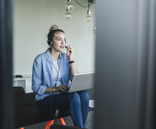 Businesswoman Sitting At Desk, Using Headset And Laptop